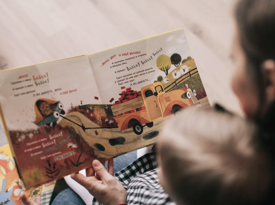 A child reading a printed book with his parent.